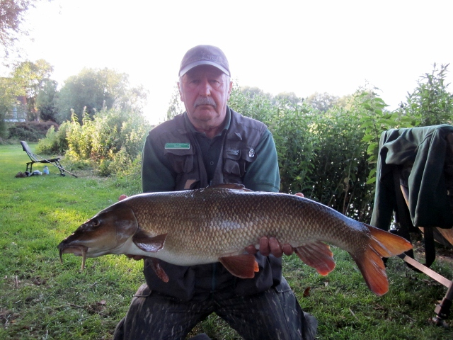 Brian Willson smiles with happiness at landing this classic looking 12lb 12oz Hampshire Avon barbel. Well done Brian, you deserved that.
